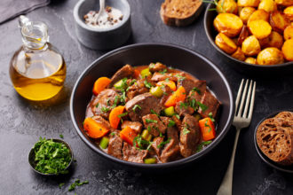 Beef meat and vegetables stew in black bowl with roasted baby potatoes. Dark background.